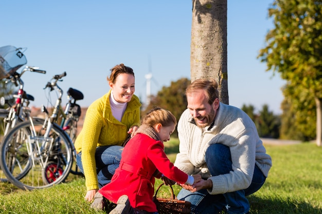 Family collecting chestnuts on bicycle trip