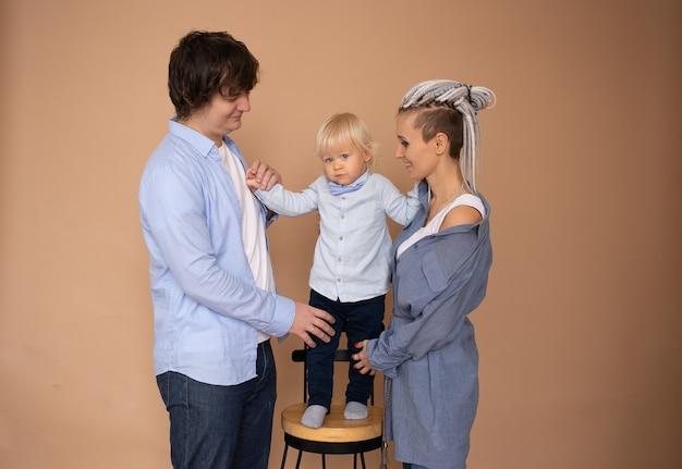 家族の概念。母と父と幼い息子がベージュの壁に隔離