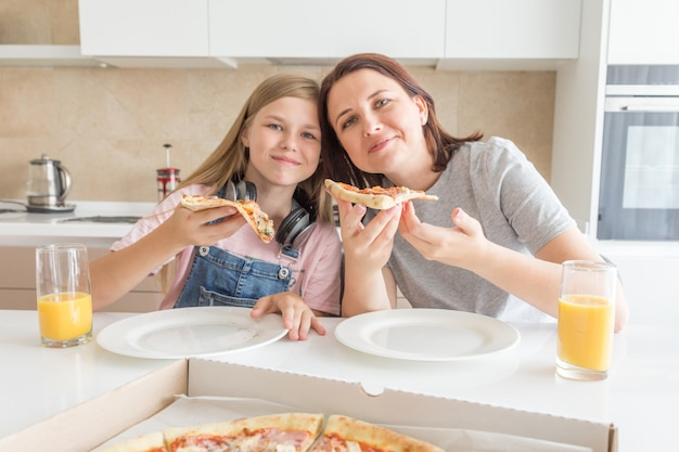 Family concept, mother and daughter eating a tasty pizza