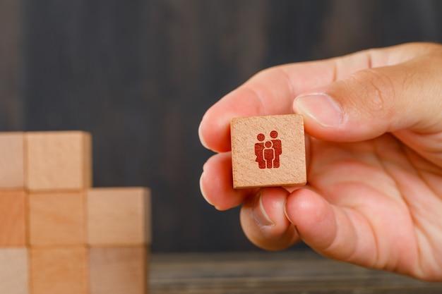 木製のテーブルの側面図の家族の概念。木製キューブを持っている手。