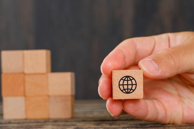 Концепция семьи на взгляде со стороны деревянного стола. рука деревянные кубики с иконами.