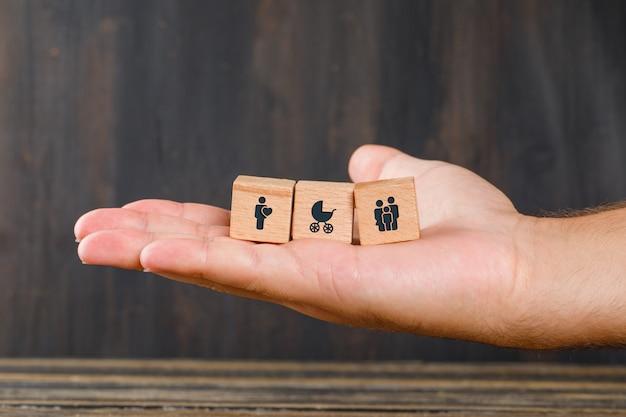 木製のテーブルの側面図の家族の概念。アイコンを持つ木製キューブを持っている手。