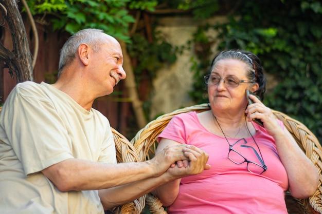 家族の概念。庭で屋外でスマートフォンを使用して老夫婦