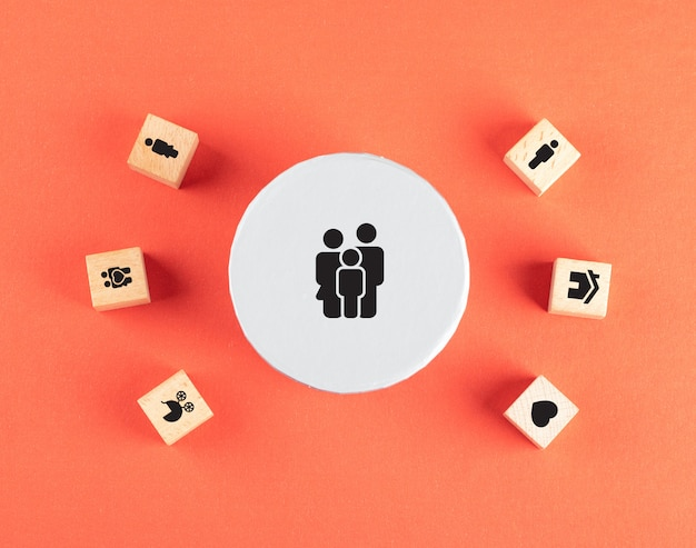 Family concept with icons on wooden cubes on red table flat lay.