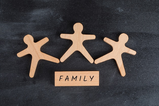Family concept with wooden block and human figures on dark grey table flat lay.