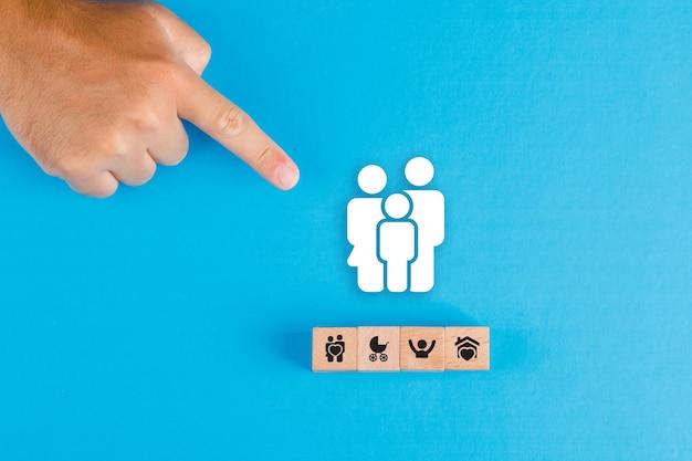 Concetto di famiglia con blocco di legno, icona della famiglia di carta sul tavolo blu laici piatta. puntamento della mano dell'uomo.