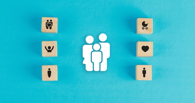 Family concept with wooden blocks, paper family icon on blue table flat lay.
