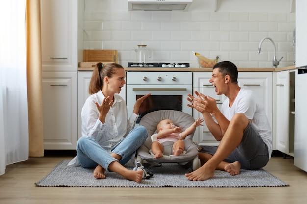 Conflitto familiare, ragazzino carino o ragazza sulla sedia a dondolo, giurando genitori seduti sul pavimento in cucina, litigando vicino a figlia o figlio neonato, avendo problemi nella loro relazione.