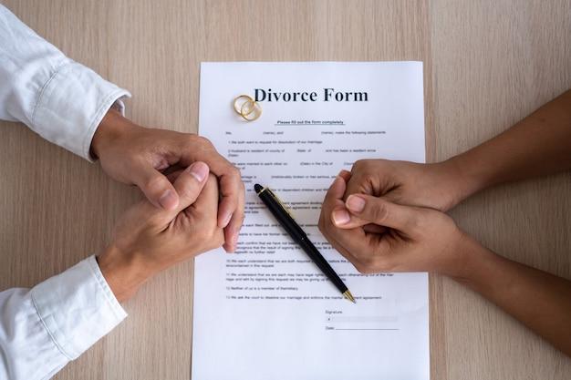 가족 갈등과 사랑 문제 개념. 이혼 서류와 함께 남편과 아내의 손. 결혼 반지는 계약에서 제거되었습니다.