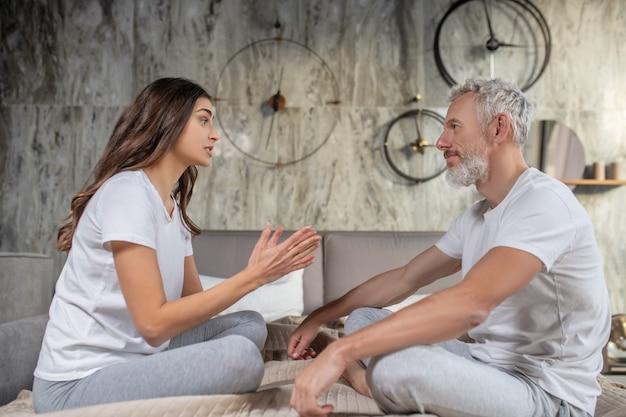 가족 대화. 심각한 젊은 여자와 성인 웃는 남자의 프로필은 침대에 서로 반대 앉아있는 동안 이야기