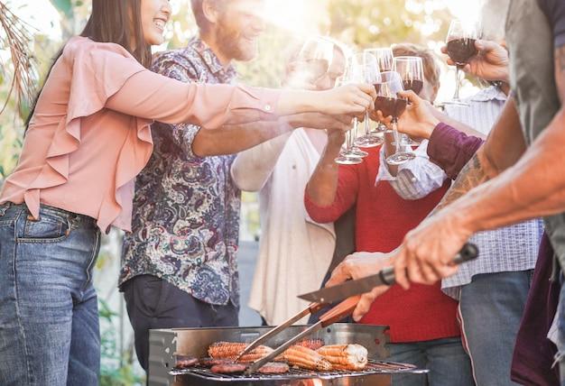 家族がハンバーガー、トウモロコシを調理し、屋外のバーベキューの食事で赤ワインで応援