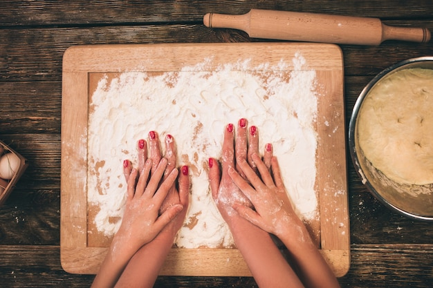 Family cooking homemade cakes, mom's and daughter 's hands in flour on a table.
