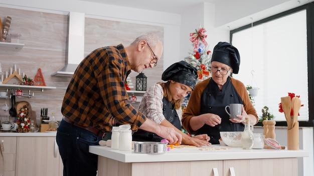 쿠키 모양을 준비하는 전통적인 진저브레드 맛있는 디저트를 요리하는 가족