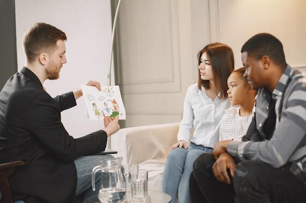 セラピストとの自宅での家族カウンセリングセッション。女の子に感情の写真を見せている心理学者