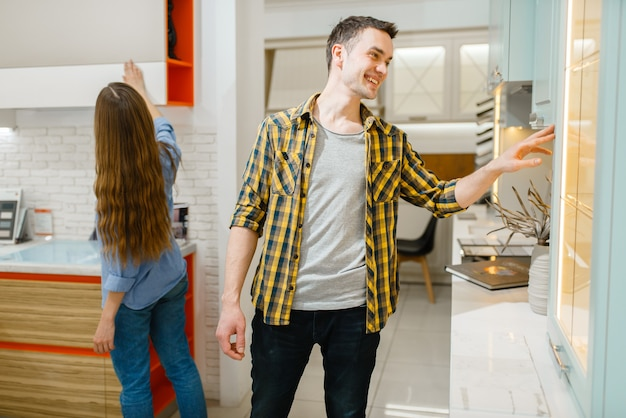 Семейная пара покупает кухонную гарнитуру в выставочном зале мебельного магазина. мужчина и женщина ищут ассортимент в магазине, муж и жена покупают товары для современного домашнего интерьера