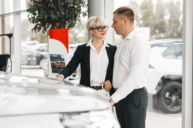 Family couple choose a car in dealership standing and looking each other. .
