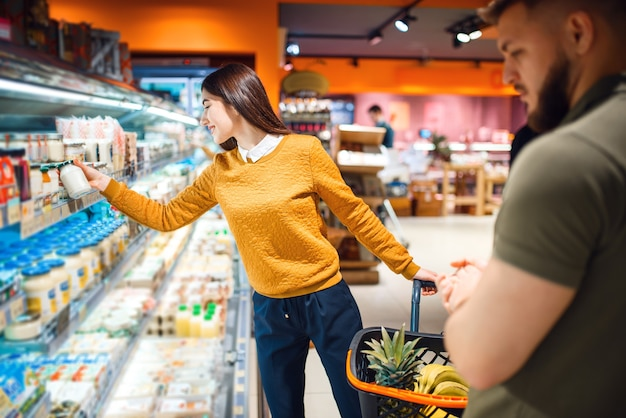Family couple choosing dairy products in grocery store