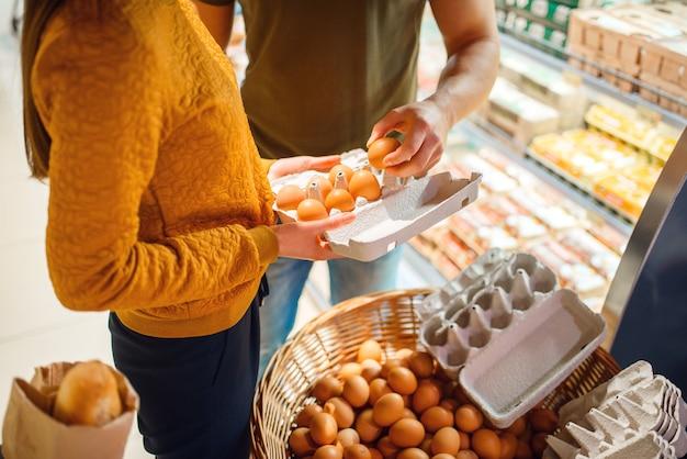 Семейная пара, выбирая яйца в продуктовом магазине