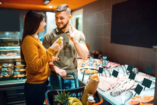 Family couple choosing oil for cooking fish in grocery store