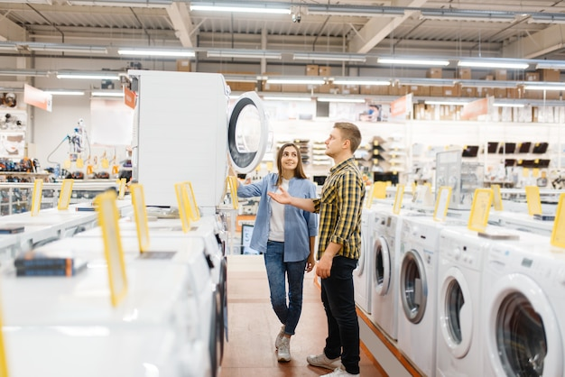 Семейная пара, выбирая стиральную машину в магазине электроники. мужчина и женщина покупают бытовые электроприборы на рынке