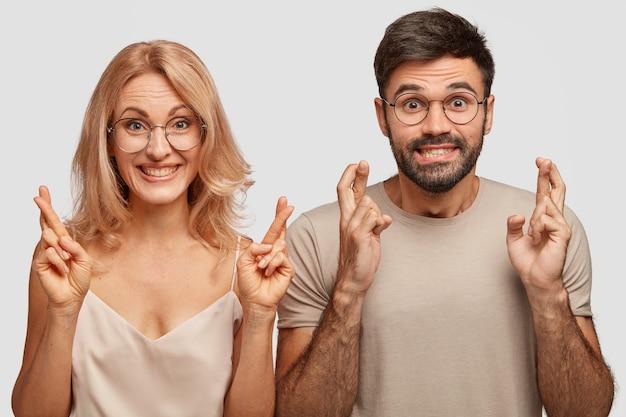 家族のカップルは指を交差させ、幸運を信じ、健康を祈る