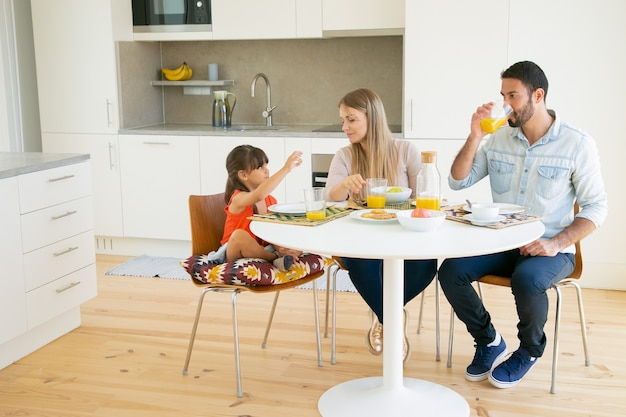 Family couple and girl having breakfast together in kitchen, sitting at dining table, drinking orange juice and talking.