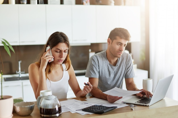 財政上の問題を抱えている家族のカップル、それらを解決しようとすること、融資を受けること、銀行に電話すること、契約に署名すること。仕事にモダンなデバイスを使用してキッチンに座っている男女