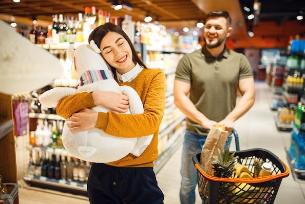 Семейная пара в продуктовом магазине, консьюмеризм
