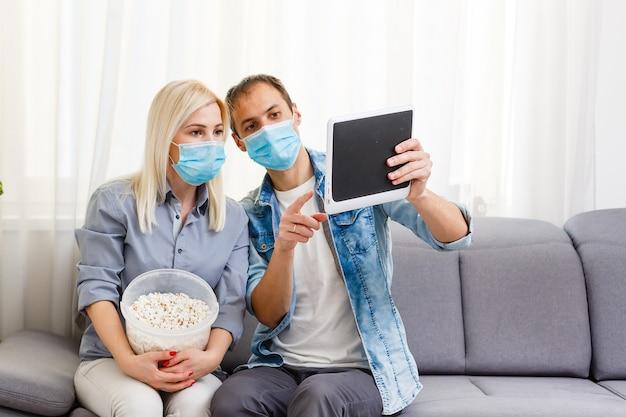 ラップトップでベッドに横たわっている医療フェイスマスクの家族のカップル。ビデオを見て、一緒に働き、covid-19コロナウイルスの流行中に検疫するという概念
