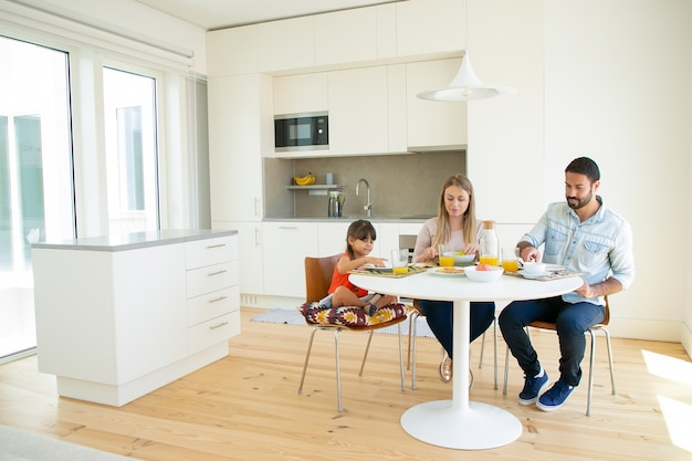 Family couple and kid having breakfast together in kitchen, sitting at dining table with dish and orange juice