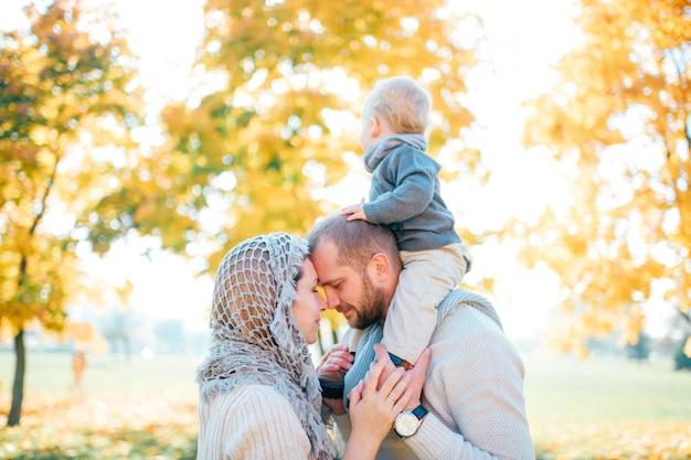 Семейная пара поцелуи на улице с их ребенком, сидя на плечах отца