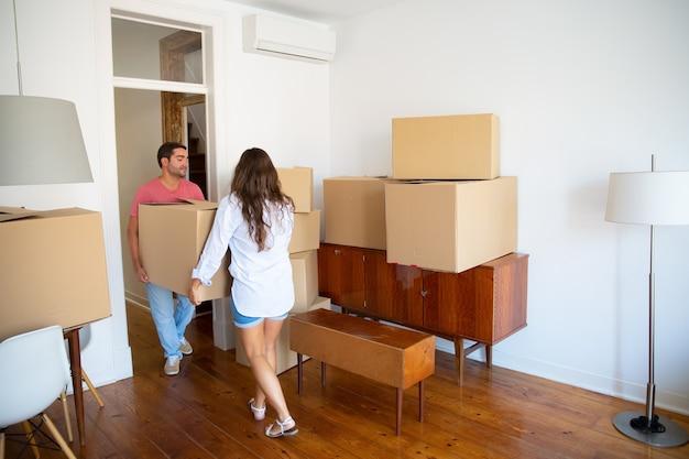 Семейная пара выходит из квартиры, неся картонные коробки и мебель