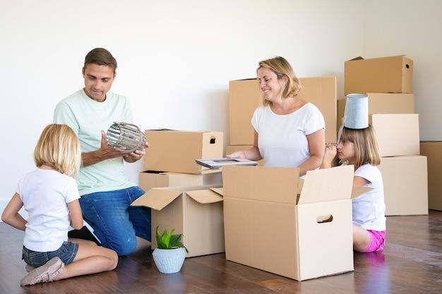 Coppia di famiglia e bambine che si trasferiscono nel nuovo appartamento, si divertono mentre disimballano le cose nel nuovo appartamento, si siedono sul pavimento e prendono oggetti da scatole aperte