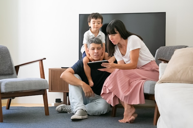 Family couple and little son using digital tablet, looking at screen, sitting in living room.