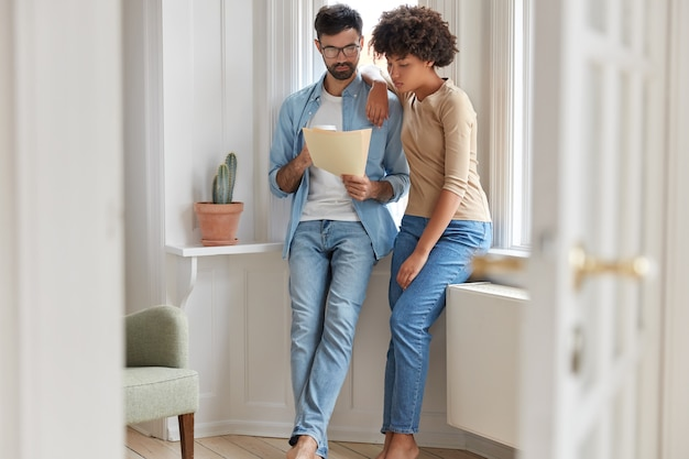Family couple look at bill, plan their budget and count expenses, dressed in jeans, drink takeaway coffee, pose in modern apartment near window. two interracial partners discuss business documents