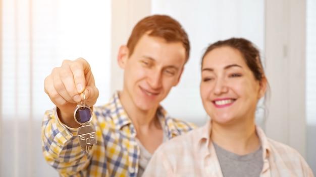 가족 부부는 창 근처에 새 아파트의 열쇠를 본다