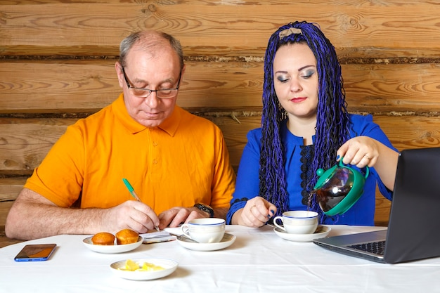 A family couple a man in glasses and a woman with blue afro braids at the table a woman pours tea a man writes information