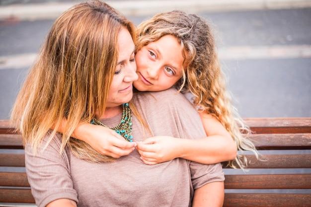 家族のカップルの母と娘が一緒に屋外の幸せな余暇活動で抱き締めて、学校に戻る前の夏の日と冬を楽しんでいます。金髪の白人のママと女の子