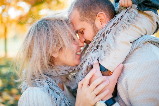 Семейные пары открытый с их ребенком, сидя на плечах отцов.