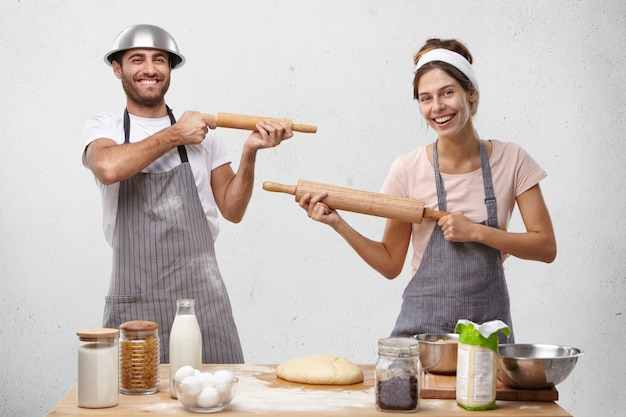 Family couple play fool on kitchen, shoot at each other with rolling pins