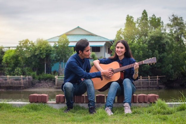 Family couple playing guitar in garden at home