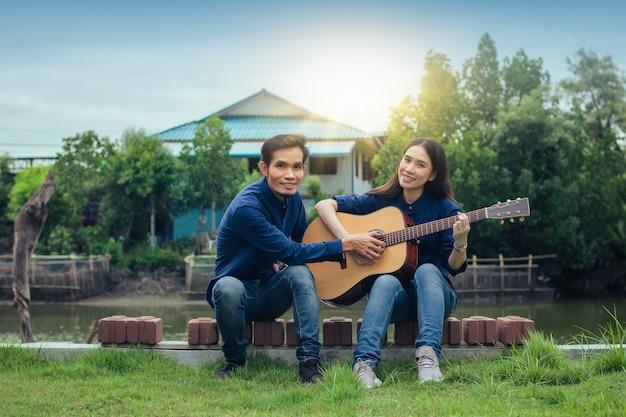 집에서 정원에서 기타를 연주하는 가족 커플