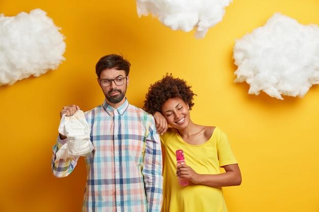 家族のカップルは出産の準備をします。妊娠中の女性と彼女の夫は哺乳瓶とおむつでポーズをとり、すぐに親になる準備ができて、新生児のために必要なものを購入し、楽しい雑用をします