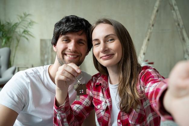 Семейная пара с гордостью показывает ключи от своего нового дома