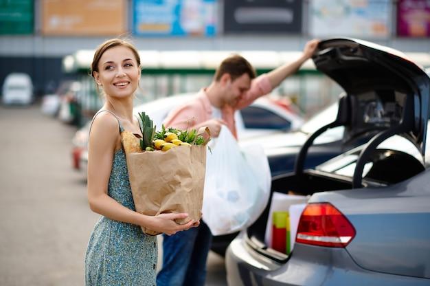 家族のカップルが購入したものをトランクに入れます