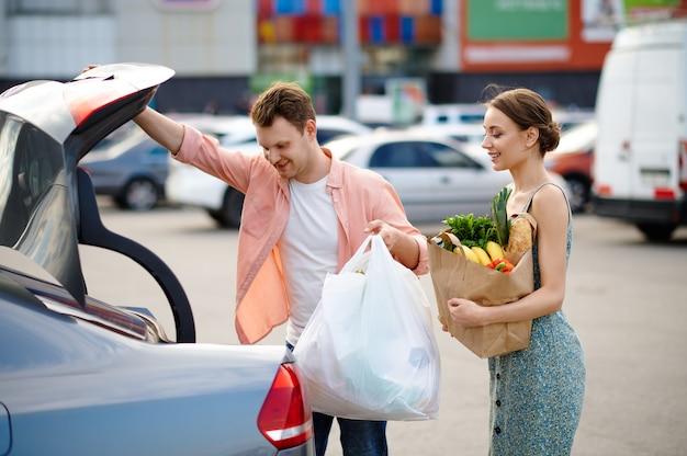 Семейная пара кладет свои покупки в багажник