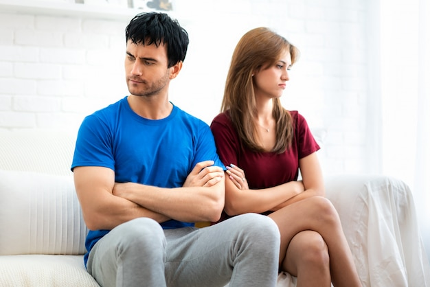 Family couple sitting on the couch not talking after argument, young husband is tired.