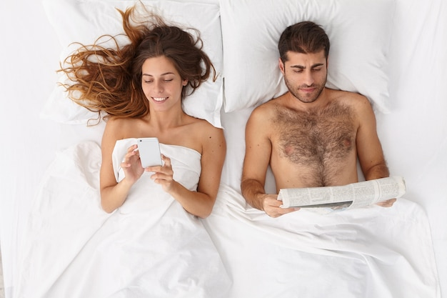 Family couple stay in comfortable bed before sleep, woman uses mobile phone for online chatting, surfs internet, addicted to moden technologies, man reads newspaper, do not talk to each other