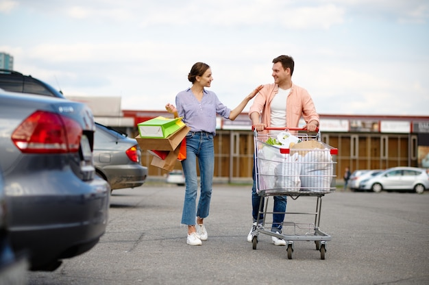 Family couple with bags in cart on car parking