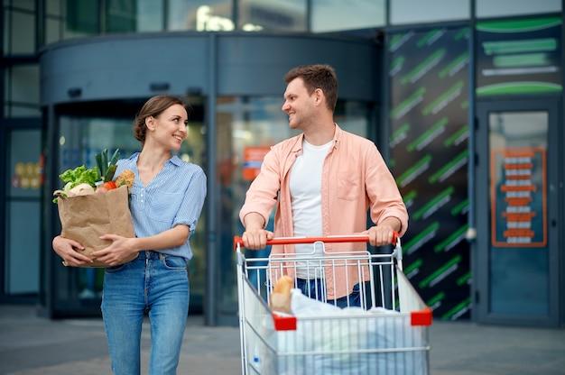市場の駐車場でカートと家族のカップル。ショッピングセンター、スーパーマーケットの男女からの購入を運ぶ陽気な顧客